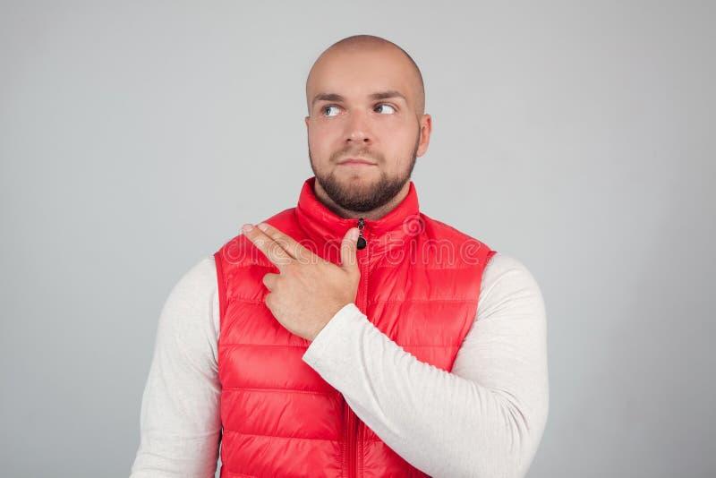 El tiro horizontal del var?n barbudo hermoso con la cabeza calva, vestido en chaleco rojo casual, mira curiosamente el asdie, pun foto de archivo