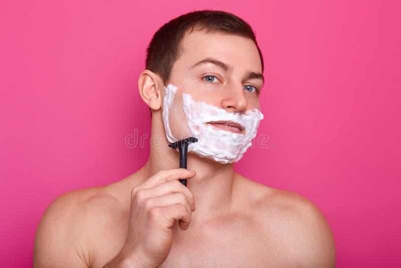 El tiro interior de la barba seria de los afeitados del hombre, tiene espuma en cara, sostiene la maquinilla de afeitar, tiene cu fotos de archivo