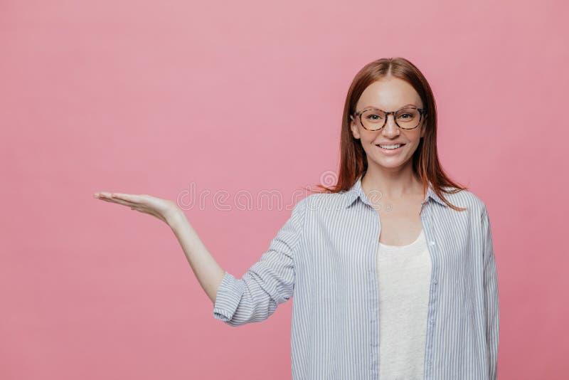 El tiro interior de la mujer europea con el aspecto agradable, sonrisa encantadora, lleva a cabo el espacio de la copia, aumenta  fotografía de archivo libre de regalías