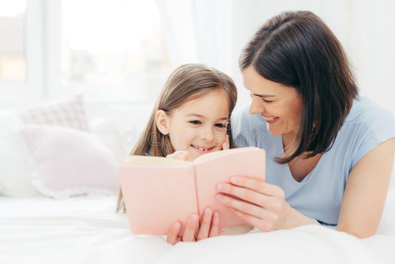 El tiro interior del niño femenino de mirada agradable con la expresión curiosa, lee el libro interesante así como su madre cariñ foto de archivo libre de regalías