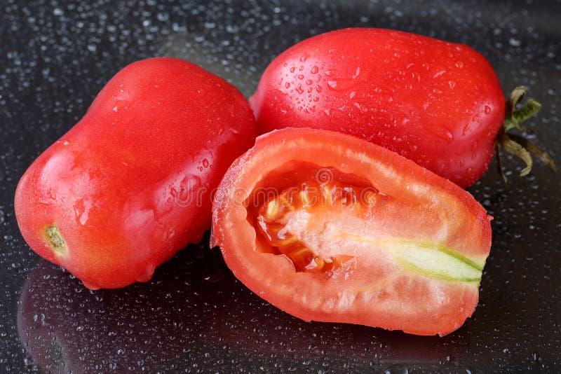El tiro macro de dos y la mitad cortaron los tomates de ciruelo rosados orgánicos en un fondo negro con descensos del agua imagen de archivo libre de regalías