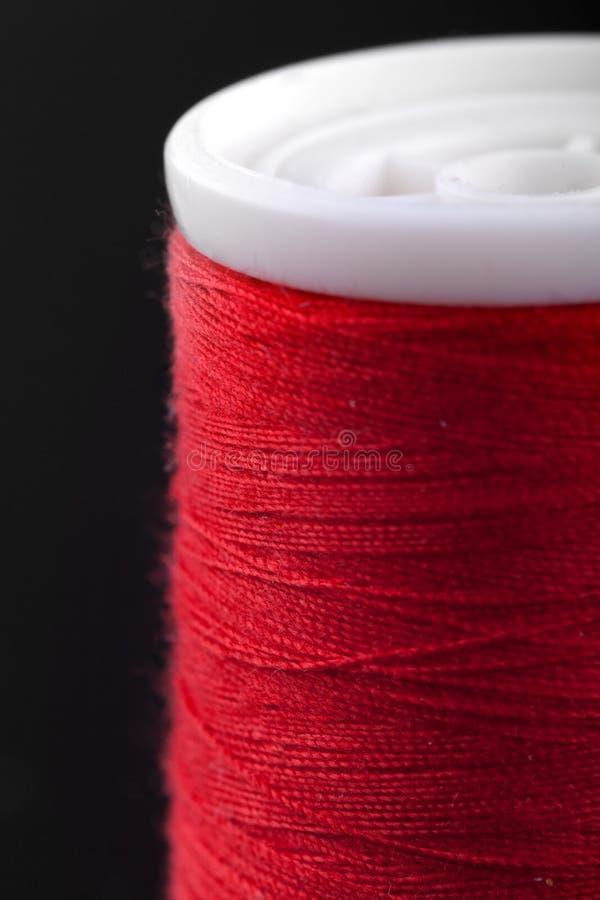 El tiro macro de la cuerda de rosca roja de la bobina isoladed en negro imagen de archivo libre de regalías