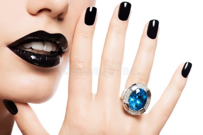El tiro macro de los labios y de los clavos de una mujer pintó el blac brillante del color imagen de archivo libre de regalías