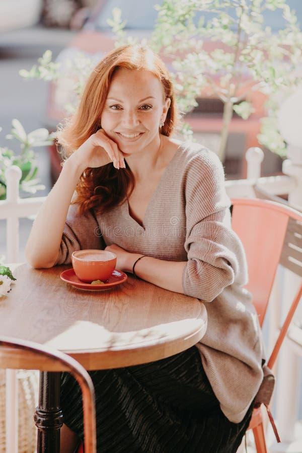 El tiro vertical de la hembra astuta alegre vestida en ropa de moda, café de las bebidas, presenta en café al aire libre, disfrut imagen de archivo libre de regalías