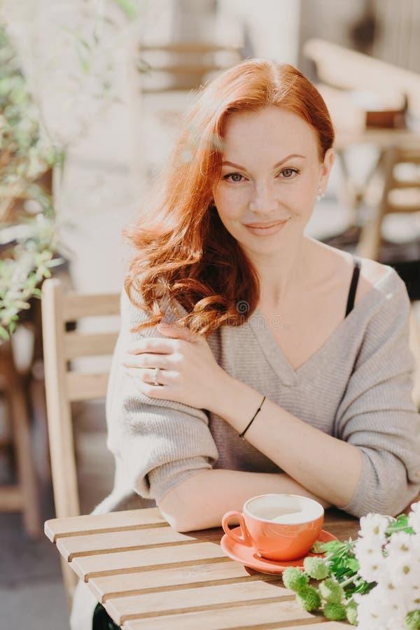 El tiro vertical de la mujer joven pelirroja atractiva con el pelo ondulado, vestido en puente caliente, bebe el café o el latte, foto de archivo libre de regalías