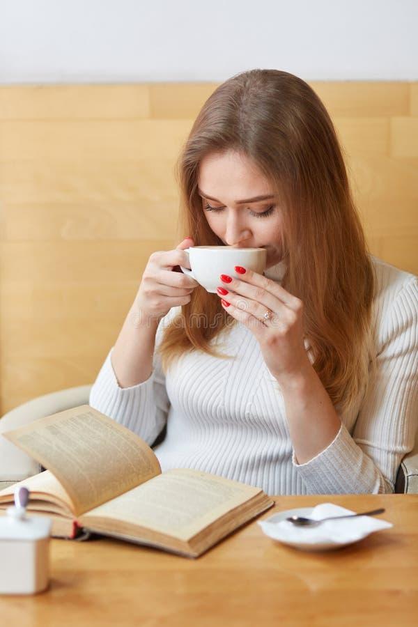 El tiro vertical de la mujer preciosa despreocupada bebe té caliente de la taza blanca, lee la historia fantástica, libro de los  foto de archivo