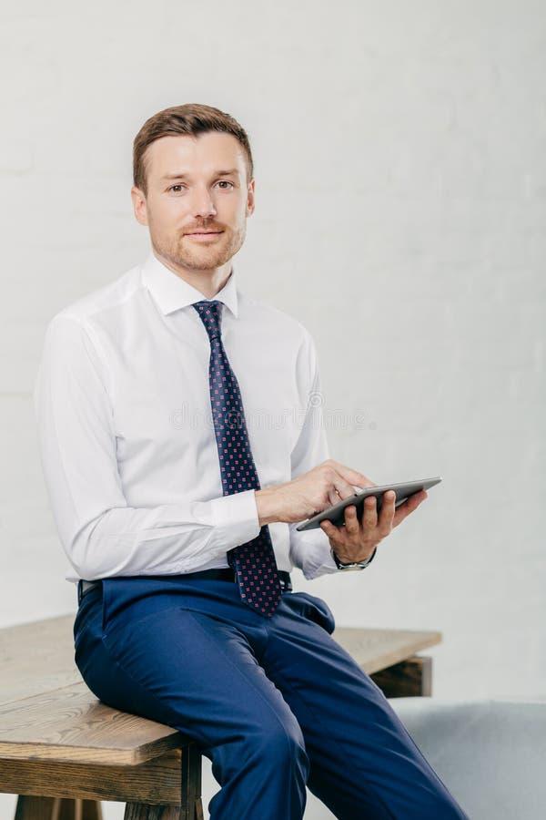 El tiro vertical del hombre de negocios serio utiliza la tableta moderna para las noticias financieras de lectura en línea, hace  fotografía de archivo