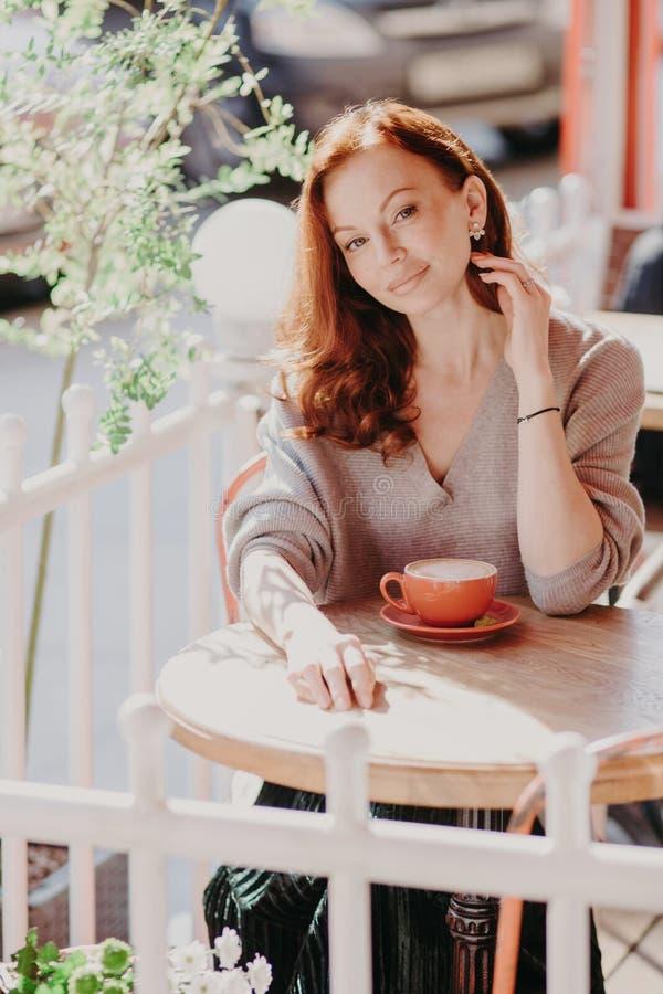 El tiro vertical del jengibre apuesto femenino con compone, se sienta en café al aire libre, bebe el café aromático o el latte, g imagen de archivo libre de regalías