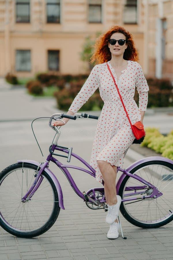 El tiro vertical del modelo femenino pelirrojo hermoso tiene resto despu?s de cubrir distancia en la bicicleta, lleva las gafas d imagen de archivo libre de regalías