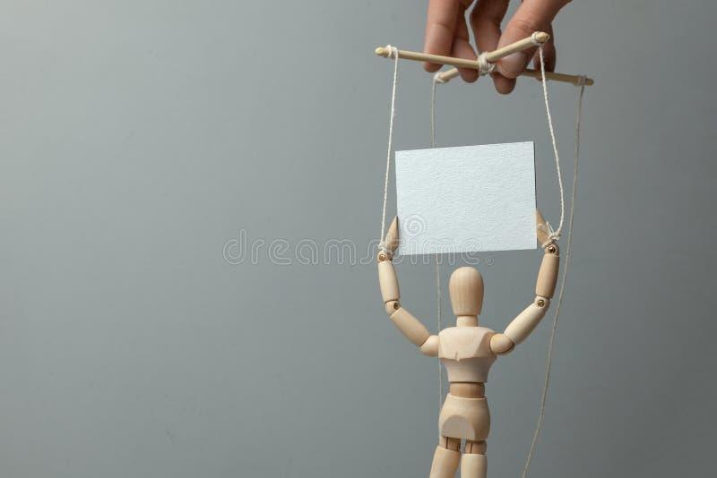 El titiritero gobierna la muñeca en las cuerdas que sostiene el cartel El concepto de reunión o de demostración con el activista  imagen de archivo