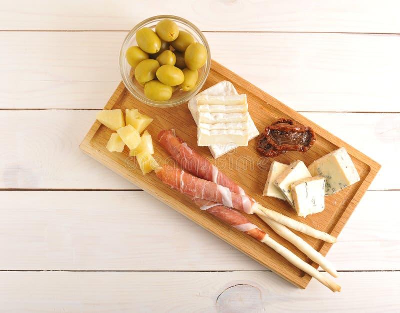 El tocino en las barras de pan, queso, secó los tomates, aceitunas en un woode foto de archivo libre de regalías