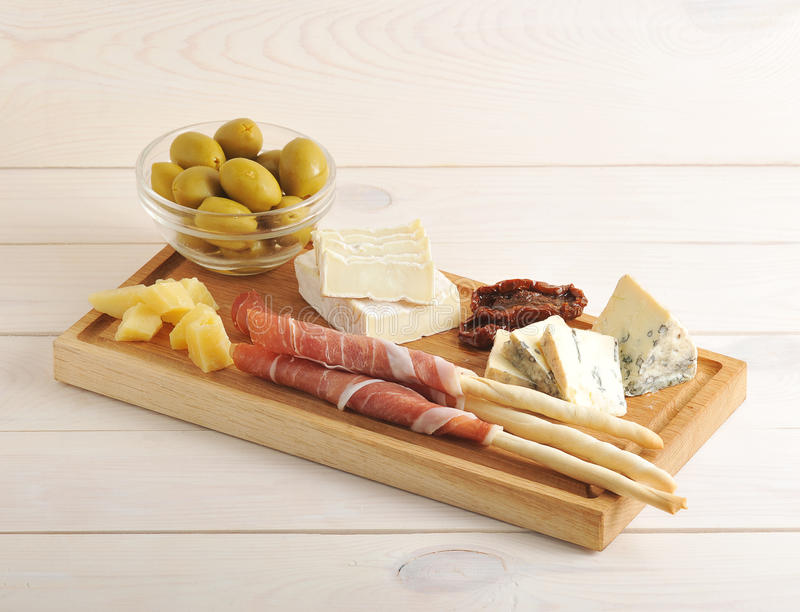 El tocino en las barras de pan, queso, secó los tomates, aceitunas en un woode fotografía de archivo libre de regalías