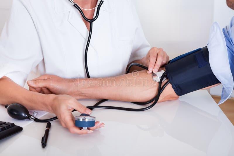 El tomar del doctor pacientes presión arterial foto de archivo