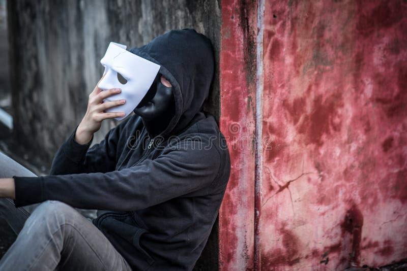 El tomar del hombre del misterio de la máscara que muestra otra máscara bajo ella fotos de archivo libres de regalías