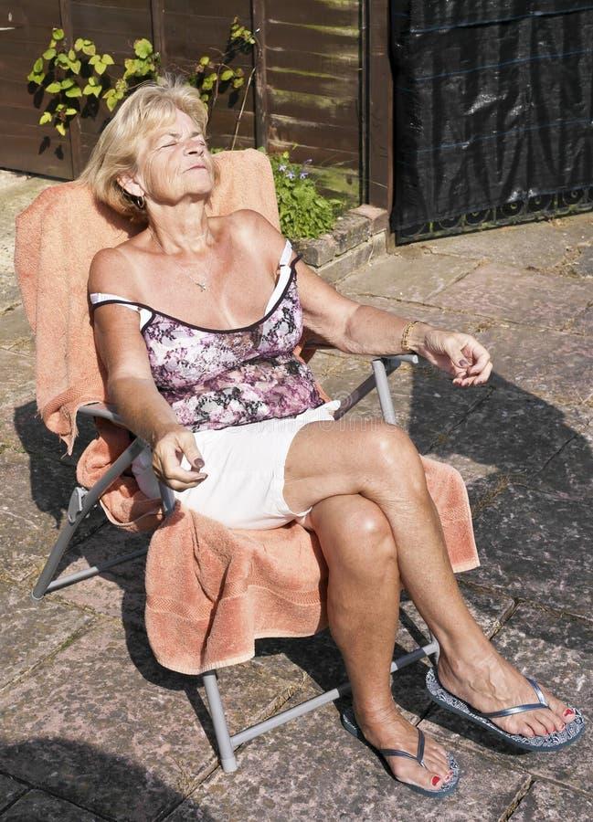 El tomar el sol mayor de la mujer imagenes de archivo
