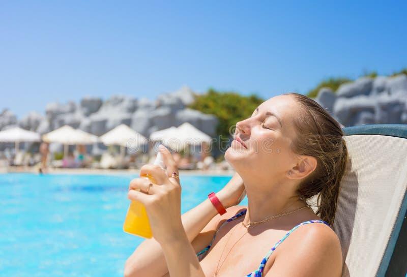 El tomar el sol seguro Mujer por la piscina de vacaciones fotos de archivo libres de regalías