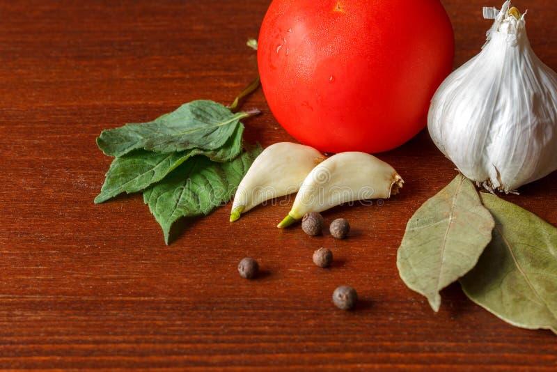 El tomate y el ajo rojos con las especias están en la tabla foto de archivo