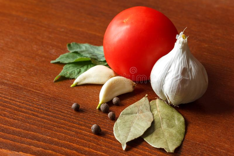 El tomate y el ajo rojos con las especias están en la tabla fotografía de archivo