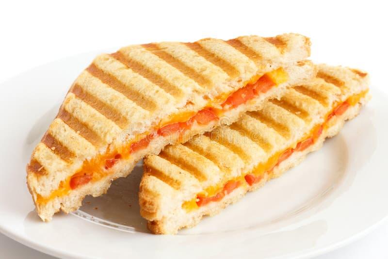 El tomate y el queso clásicos tostaron el bocadillo en la placa blanca imagen de archivo