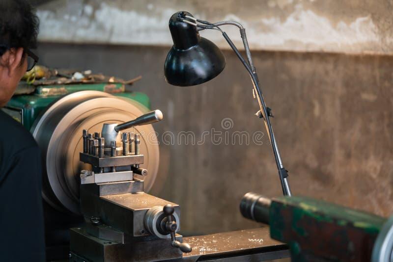 El torno automotriz del metal de las partes de rotación es una herramienta que gira el objeto sobre un eje de la rotación para re foto de archivo libre de regalías