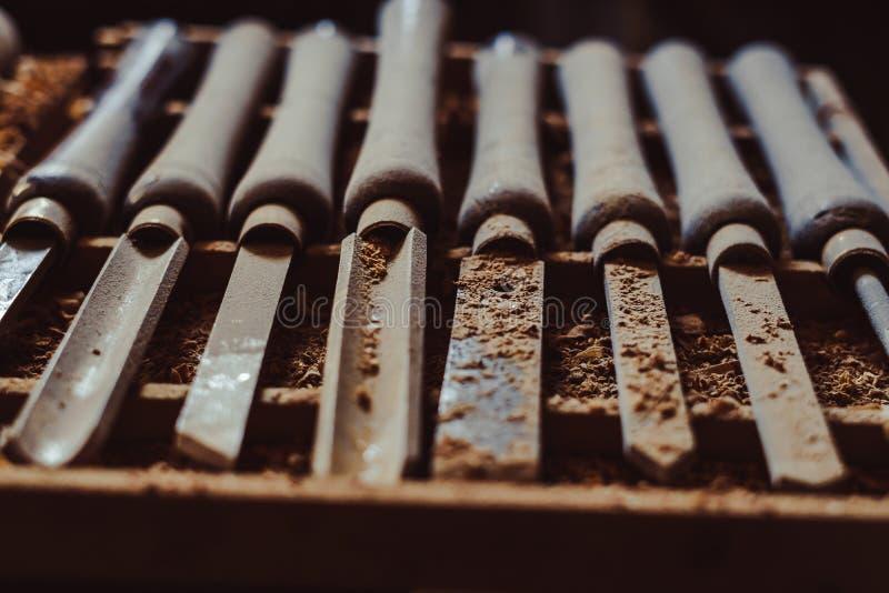 El torno de madera usado viejo cincela la selección en la tabla de madera oscura imagenes de archivo