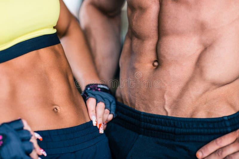 El torso del hombre muscular y de la mujer deportiva imagenes de archivo