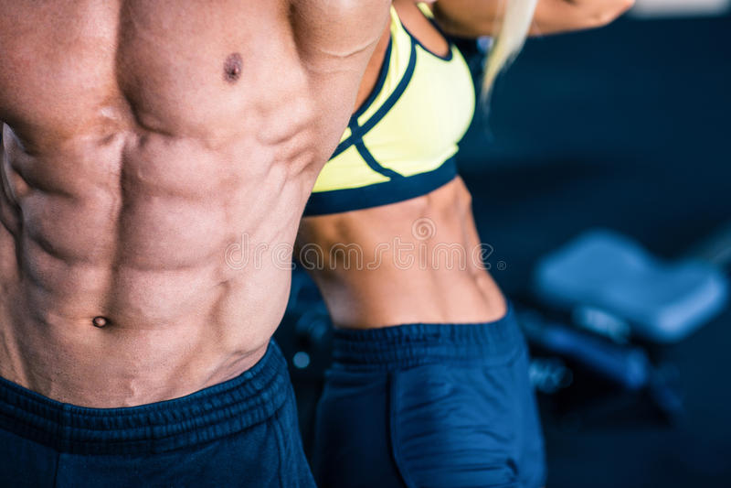 El torso del hombre muscular y de la mujer fuerte fotos de archivo