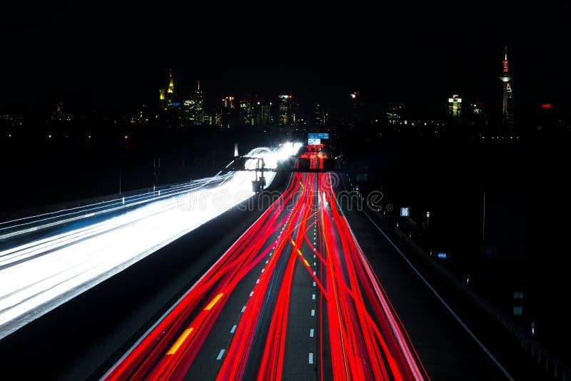 El tráfico de la noche se arrastra en la carretera, horizonte Francfort Alemania fotos de archivo libres de regalías