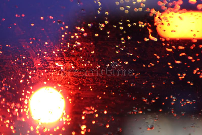 El tr?fico se ve a trav?s del parabrisas del coche cubierto en lluvia, fondo hermoso de la lluvia y de las luces imagenes de archivo
