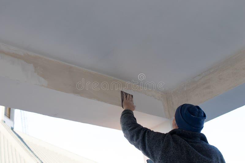 El trabajado cualificado separa el estuco y la pintura en un haz de una terraza d fotografía de archivo libre de regalías