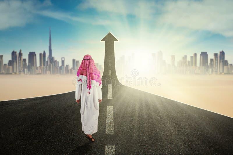 El trabajador árabe camina en el camino con la flecha fotografía de archivo