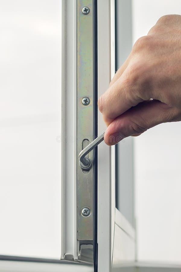 El trabajador ajusta la operación de la ventana plástica fotos de archivo