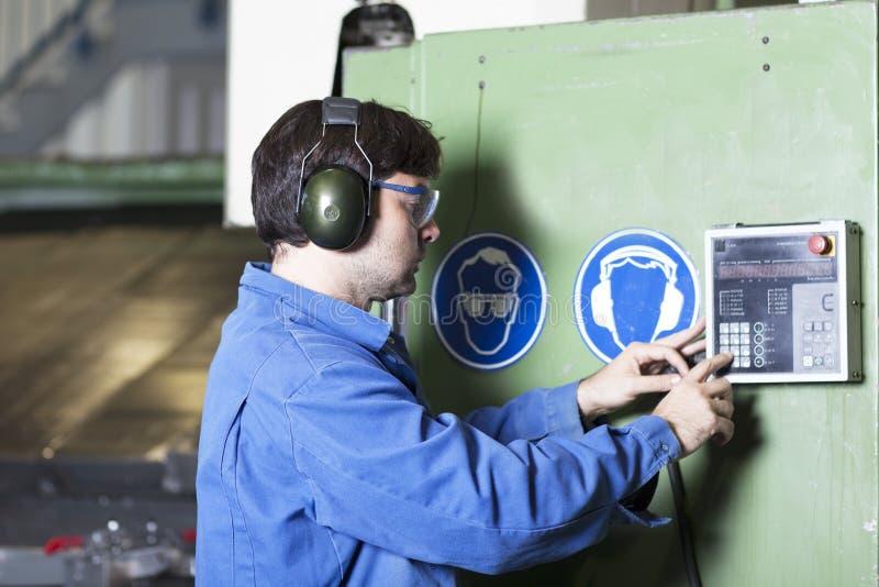 El trabajador ajusta una máquina en fábrica fotos de archivo