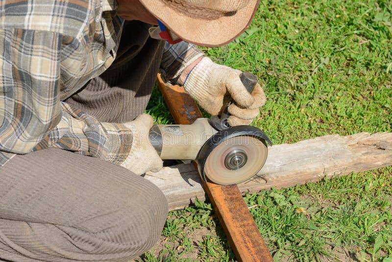 El trabajador asierra un perfil del metal imágenes de archivo libres de regalías