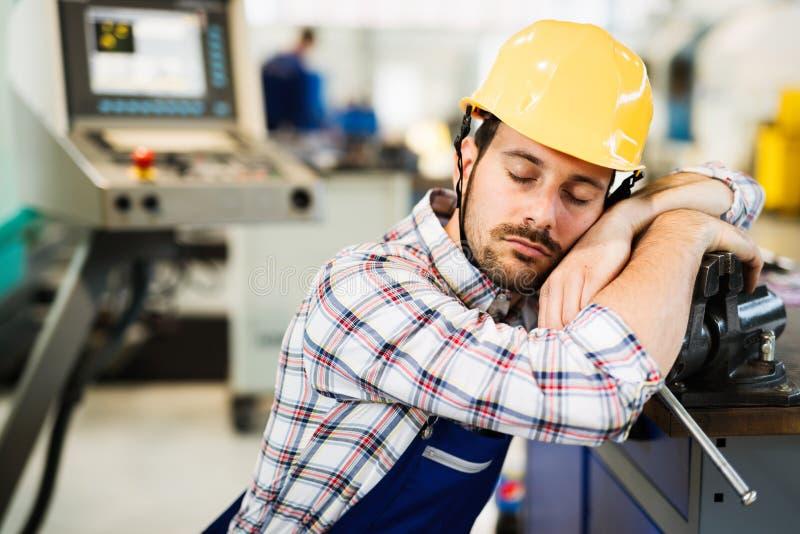 El trabajador cansado se cae dormido durante horas de trabajo en fábrica imagen de archivo libre de regalías