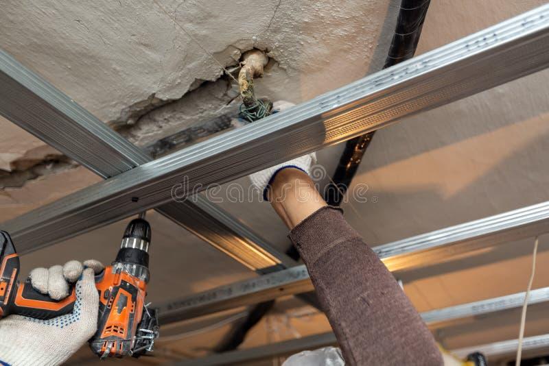 El trabajador con los guantes protectores est? perforando por el perforador el techo para instalar marcos del metall en el aparta imagenes de archivo