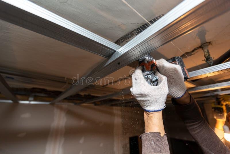 El trabajador con los guantes protectores est? perforando por el perforador el techo para instalar marcos del metall en el aparta foto de archivo libre de regalías