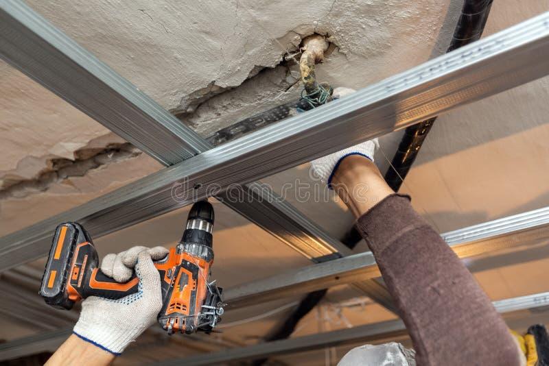 El trabajador con los guantes protectores est? perforando por el perforador el techo para instalar marcos del metall en el aparta fotografía de archivo libre de regalías