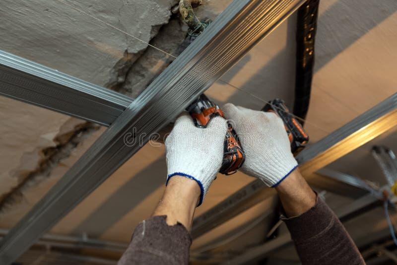 El trabajador con los guantes protectores est? perforando por el perforador el techo para instalar marcos del metall en el aparta fotografía de archivo