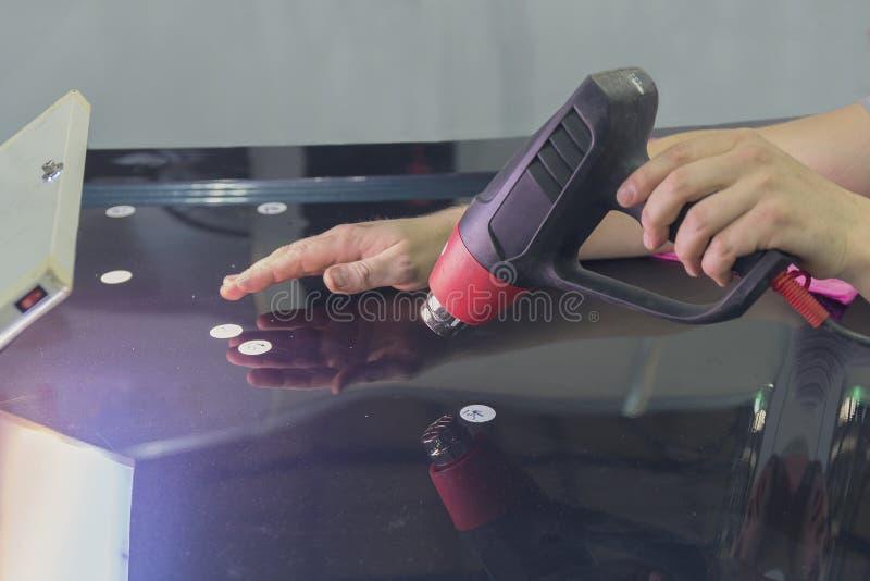 El trabajador con un secador de pelo está haciendo trabajos sobre enderezar los coches imagen de archivo libre de regalías