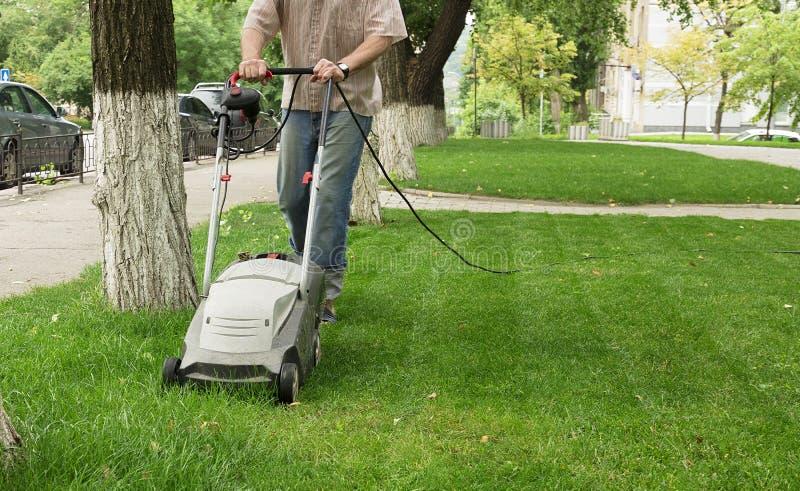 El trabajador corta la alta hierba con un cortacésped eléctrico industrial foto de archivo libre de regalías