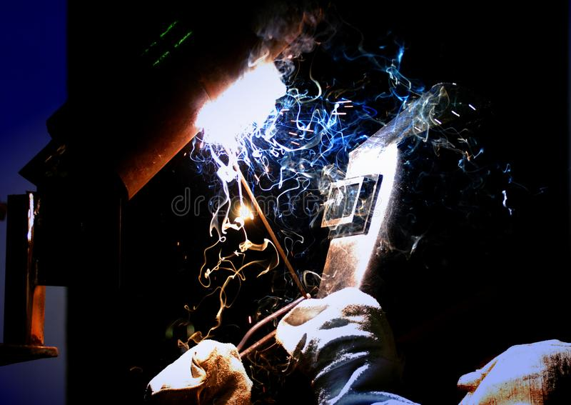 El trabajador corta la soldadora del soldador del metal foto de archivo