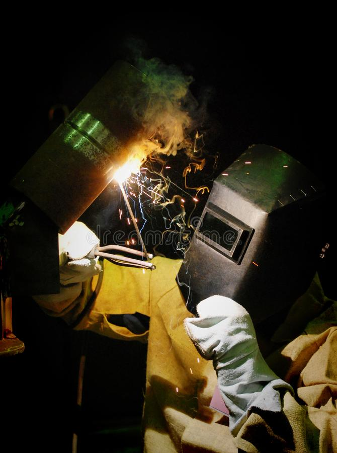 El trabajador corta la soldadora del soldador del metal imagen de archivo libre de regalías