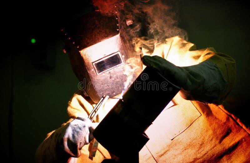 El trabajador corta la soldadora del soldador del metal fotografía de archivo
