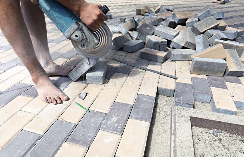 El trabajador corta las losas para poner en la terraza fotografía de archivo libre de regalías
