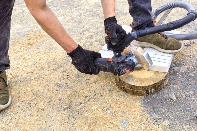 El trabajador corta una placa de metal y losas para poner en la terraza con una amoladora de ángulo imagen de archivo