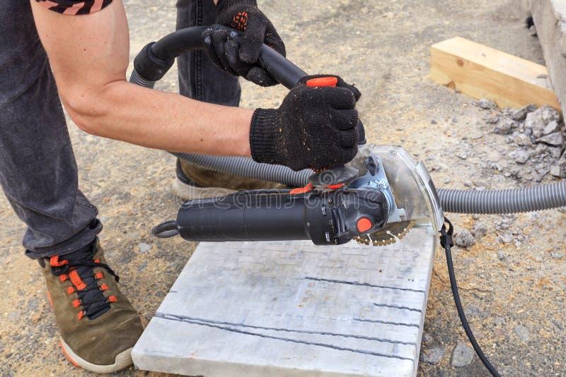 El trabajador corta una placa de metal y losas para poner en la terraza con una amoladora de ángulo foto de archivo