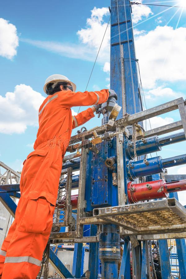 El trabajador costero de la plataforma petrolera prepara la herramienta y el equipo para los gases de la perforación bien en la p foto de archivo