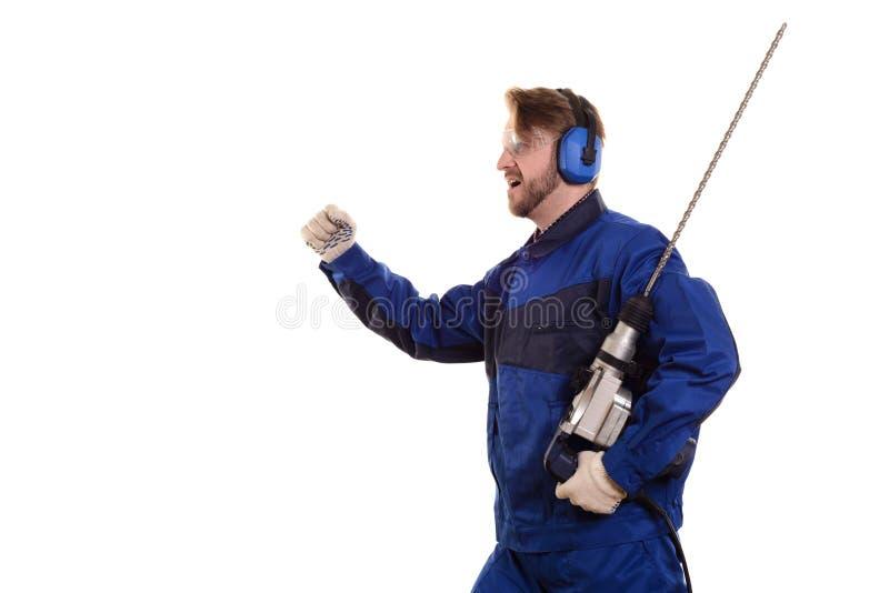 El trabajador de construcción con un puncher corre en un fondo blanco fotos de archivo libres de regalías