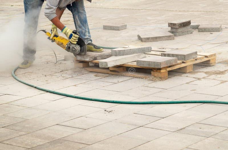 El trabajador de construcción corta el encintado de la calzada con la circular vio El hombre protege la audiencia contra peligros foto de archivo